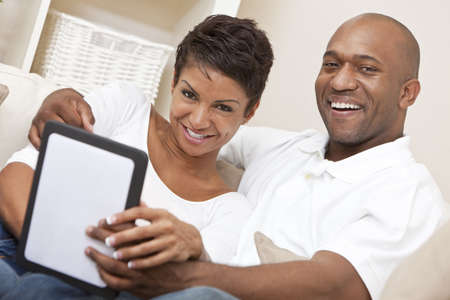 African American Man Woman Couple Using Tablet Computer photo