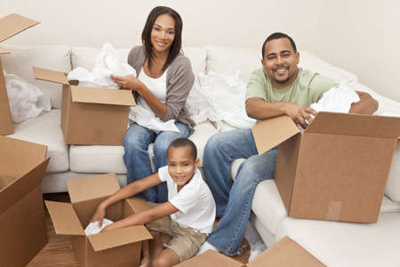 African American family, parents and son, unpacking boxes and moving into a new home, The adults are unpacking crockery and houseware. photo