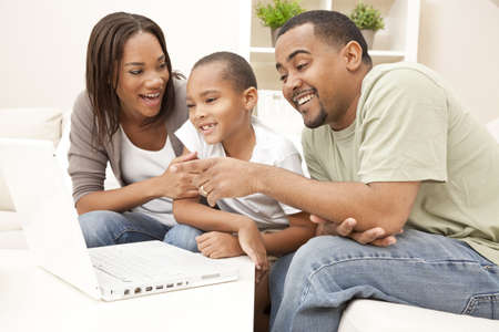 African American family, parents and son, having fun using a laptop computer together Standard-Bild