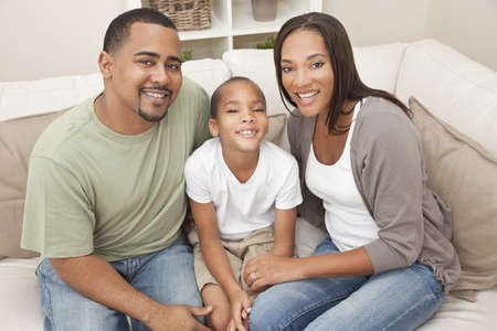 family on couch: A happy African American man, woman and boy, father, mother and son, family sitting together at home Stock Photo