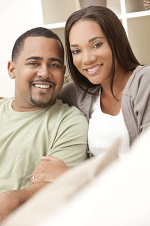 african american couple: A happy African American man and woman couple in their thirties sitting at home Stock Photo