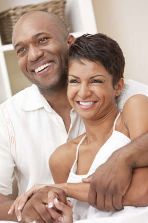 A happy African American man and woman couple in their thirties sitting at home together smiling.