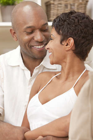 A happy African American man and woman couple in their thirties sitting at home together smiling looking at each other. photo