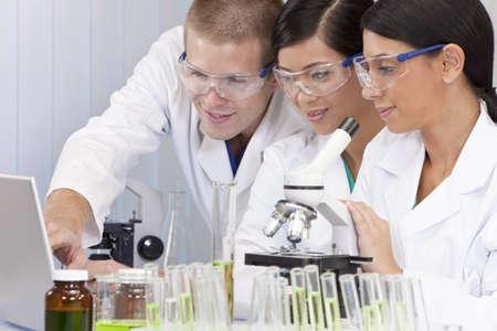 estudiantes medicina: Interracial equipo de investigadores médicos o científicos masculinos y femeninos o los médicos que utilizan un ordenador portátil y microscopio en un laboratorio.