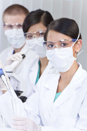 A female medical or scientific researcher or doctor using a pipette and test tube of clear liquid in a laboratory with her team of colleagues out of focus behind her. photo