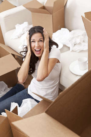 A beautiful single young woman screaming with stress while unpacking boxes and moving into a new home. Stock Photo