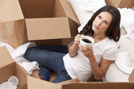 unpacking: A beautiful single young woman drinking tea or coffee unpacking boxes and moving into a new home.
