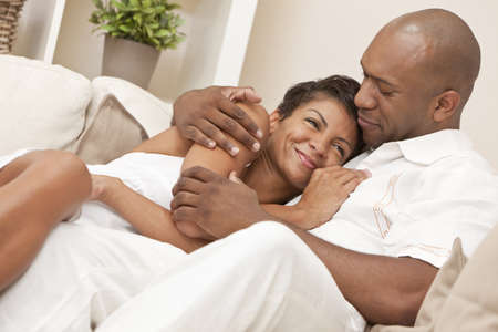 pareja de esposos: Un feliz hombre afroamericano y joven mujer en sus treinta a�os sentado en su casa, juntos, sonriente y abrazos Foto de archivo