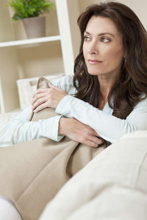 Indoor portrait of a beautiful young brunette woman in her thirties or forties holding a cushion and looking thoughtful photo