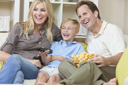 An attractive happy, young family of mother, father and son sitting on a sofa at home llaughing watching television and eating a snack photo