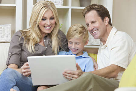An attractive happy, young family of mother, father and son sitting on a sofa at home using a laptop computer photo