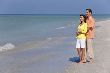 Man and woman romantic couple in embracing on a deserted tropical beach with bright clear blue sky Stock Photo - 12328924
