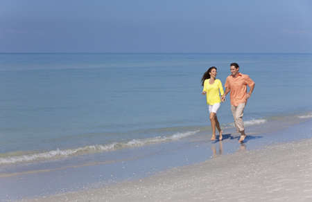 Man and woman romantic couple running holding hands on a deserted tropical beach with bright clear blue sky photo