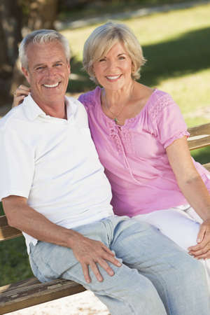 Happy senior man and woman couple sitting together outside in sunshine Standard-Bild
