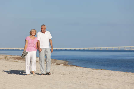 Happy senior man and woman couple together holding hands and walking on a deserted tropical beach  photo