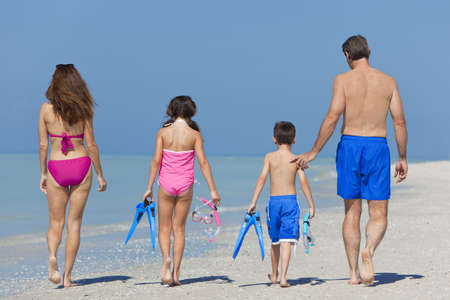 A happy family of mother, father and child, a daughter, walking in swimming costumes on a sunny beach photo