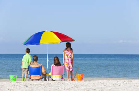 Rear view of a happy family of mother & father, parents daughter & son children having fun in deckchairs under an umbrella on a sunny beach Stock Photo - 12328909