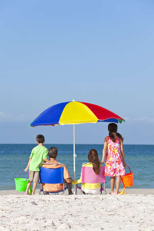 Vista trasera de una familia feliz de los ni�os de la madre y padre, hija de padres e hijo se divierten en tumbonas bajo una sombrilla en una playa soleada