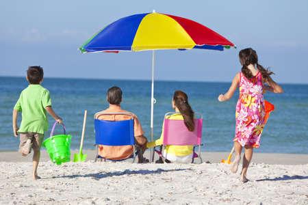 Vista trasera de una familia feliz de los niños de la madre y padre, hija de padres e hijo se divierten en tumbonas bajo una sombrilla en una playa soleada