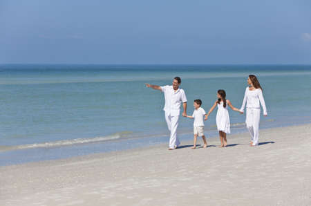 guy on beach: A happy family of mother, father and two children, son and daughter, walking holding hands and having fun in the sand on a sunny beach