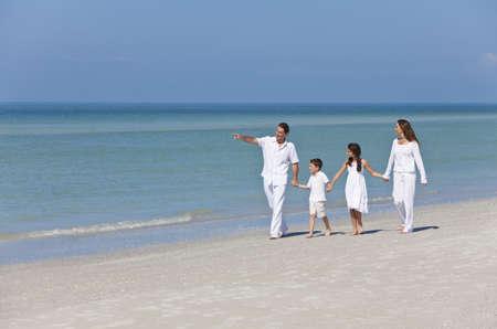 walking alone: Una familia feliz de la madre, el padre y sus dos hijos, hijo e hija, caminando tomados de la mano y divertirse en la arena en una playa soleada