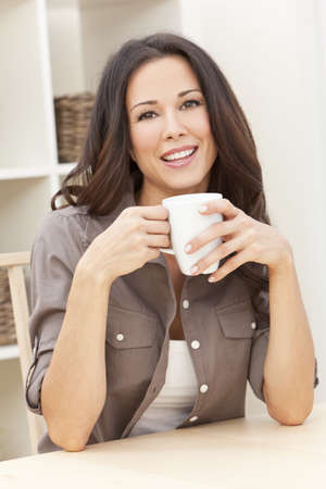 Beautiful, smiling, young brunette woman at home at a table drinking a mug of tea or coffee photo