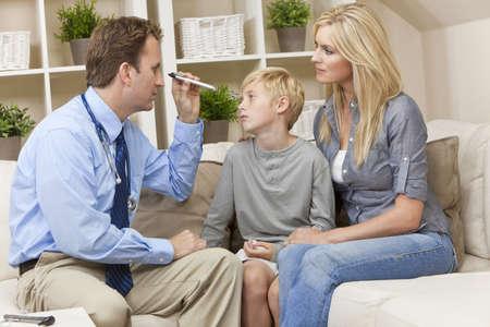 male doctor: Un medico di sesso maschile esaminando un bambino malato ragazzo con sua madre durante una visita a domicilio Archivio Fotografico
