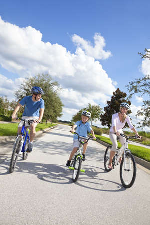 family exercise: A young family of man and woman parents and one boy child, cycling together.