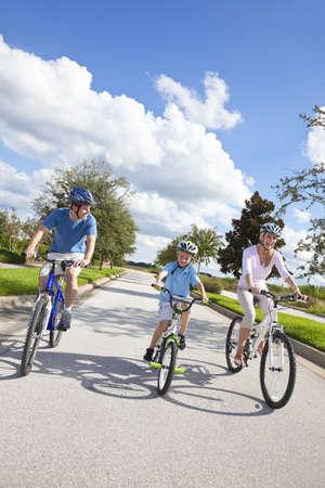 family one: Una giovane famiglia di genitori uomo e donna e un ragazzino, in bicicletta insieme. Archivio Fotografico