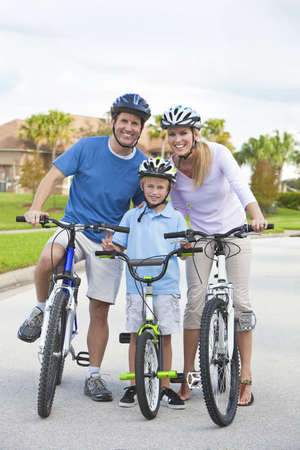 A young family of man and woman parents and one boy child, cycling together. photo