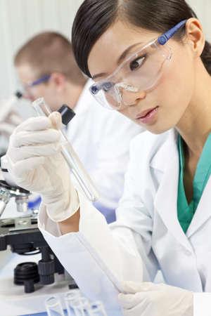 investigador cientifico: Un chino de Asia investigadora cient�fica o m�dica o un m�dico con mirar un tubo de ensayo con l�quido transparente en un laboratorio con su colega fuera de foco detr�s de ella.