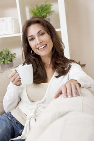 A beautiful woman in her thirties relaxing and drinking tea or coffee from a white cup at home on her sofa Stock Photo - 12328928