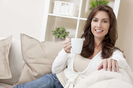 A beautiful woman in her thirties relaxing and drinking tea or coffee from a white cup at home on her sofa Standard-Bild