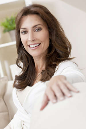Portrait of a beautiful young brunette woman in her thirties sitting at home and smiling
