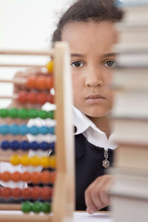 A beautiful young mixed race African American girl reading in a school classroom with a pile of books in front of her using an abacus Stock Photo - 12328956
