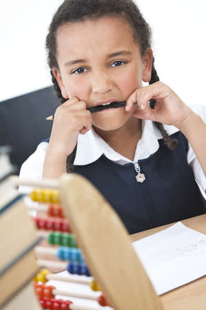 A beautiful young mixed race African American girl reading in a school classroom with a pile of books in front of her, an abacus na chewing a pencil Stock Photo - 12328925