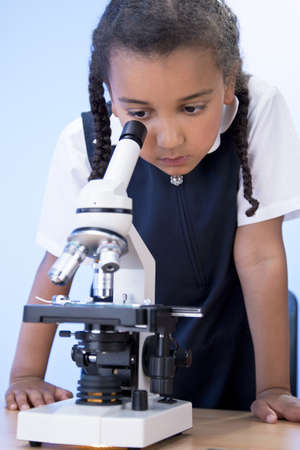 A beautiful young mixed race African American girl child using a microscope in a school laboratory photo