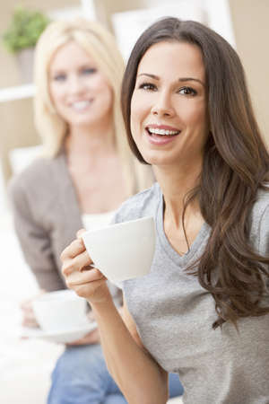 Two beautiful young women friends or girls with perfect smiles drinking tea or coffee from a white cup at home on a sofa Stock Photo - 12328939