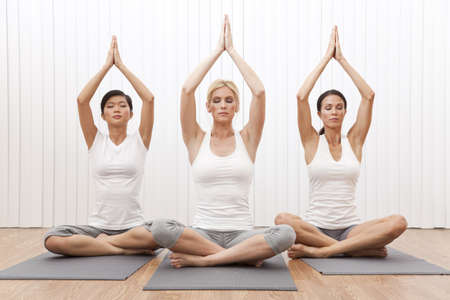 An interracial group of three beautiful young women sitting cross legged in a yoga position at a gym