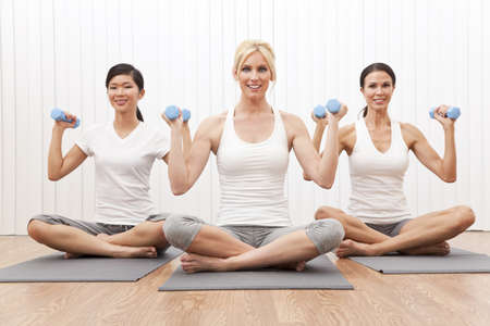 An interracial group of three beautiful young women sitting cross legged in a yoga position at a gym and weight training photo
