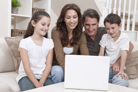 Happy family, parents, son and daughter, having fun using laptop computer together at home on a sofa. Stock Photo - 12328935