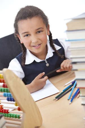 school girl uniform: A beautiful young mixed race African American girl writing or drawing in a school classroom surrounded by books and an abacus Stock Photo