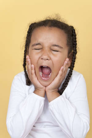 Studio shot of a beautiful young mixed race African American girl shouting or screaming maybe in pain or with toothache Stock Photo - 12813510