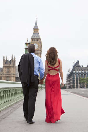 english famous: Rear view of romantic man and woman couple on Westminster Bridge with Big Ben in the background, London, England, Great Britain