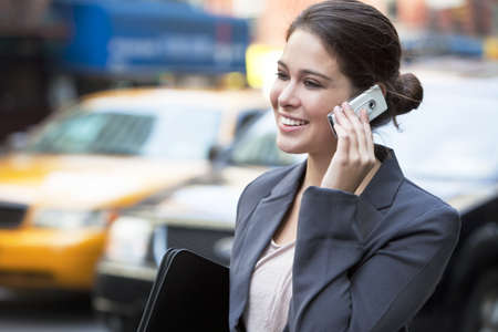 A happy young woman talking on her mobile cell phone in New York City with a yellow taxi cab behind her  Stock Photo