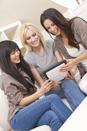 Three beautiful young women friends at home using tablet computer and laughing photo