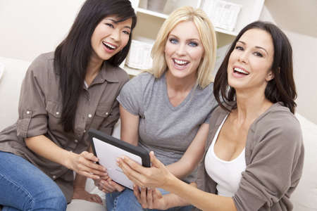 Three beautiful young women or girl friends at home using tablet computer and laughing Stock Photo
