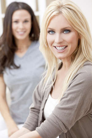 Two beautiful young women friends at home sitting on sofa or settee smiling Stock Photo - 12813931