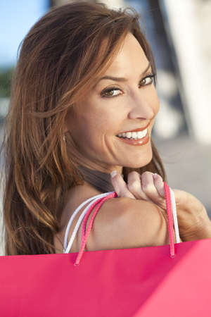 Beautiful, happy and fashionable woman with pink shopping bag photo