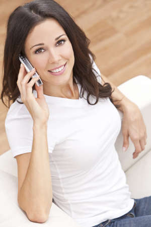 settee: Beautiful young brunette woman at home sitting on sofa or settee using her mobile cell phone and smiling